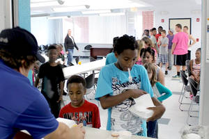 Many kids in line to get meals, multiple ages
